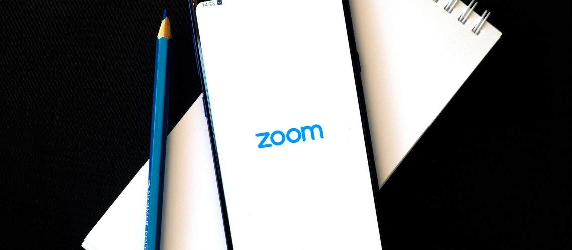 flat-lay-image-of-a-smartphone-with-zoom-icon-on-screen-isolated-on-black-zoom-is-one-of-the-popular_t20_pLK21j (1)